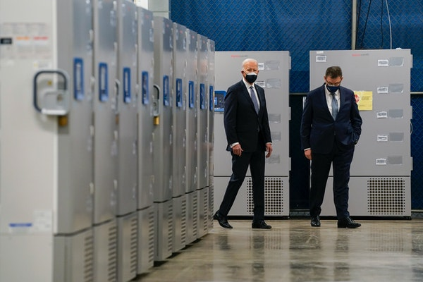 In this Feb. 19, 2021, file photo President Joe Biden walks by freezers used to hold the Pfizer COVID-19 vaccine as he tours a Pfizer manufacturing si