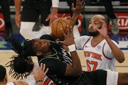 Naz Reid, left, of the Minnesota Timberwolves looks to shoot as Taj Gibson, right, of the New York Knicks defends during the first half of an NBA bask