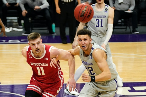 Wisconsin forward Micah Potter, left, and Northwestern forward Pete Nance chased the ball during the first half Sunday night in Evanston, Ill.