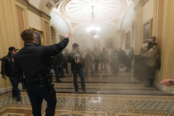 Smoke fills the walkway outside the Senate Chamber as insurrectionists loyal to President Donald Trump are confronted by U.S. Capitol Police officers