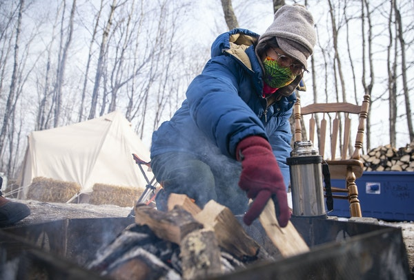Alex Golden-Wolf worked on keeping the fire going inside Camp Migizi, a small encampment next to the Enbridge Line 3 construction site in Cloquet, MN.