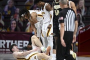 Gophers center Liam Robbins (0) grabbed his lower left leg after a hard fall in the second half against Purdue earlier this month.