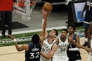 Milwaukee's Brook Lopez blocks a shot by Timberwolves center Karl-Anthony Towns during the first half Tuesday.