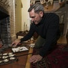 Bill Summerville makes full use of his fireplace and its tools to cook gourmet meals, including oysters on an antique grill plate.