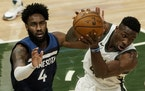 Thanasis Antetokounmpo of the Bucks and Jaylen Nowell of the Wolves go after a loose ball Tuesday night in Milwaukee.
