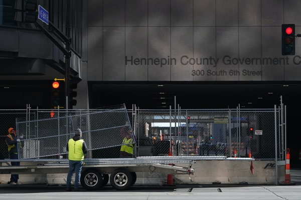 Crews with Hansen Bros Fence positioned concrete barriers, chain link fence, and concertina wire around the Hennepin County Public Safety Facility, He