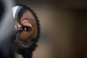 Dynasty Born Asia watched through a mirror as makeup artist Morayo Allibalogun worked on her face during the Kings and Queens Day event at YouthLink,
