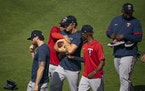 Minnesota Twins infielder Luis Arraez, and Minnesota Twins infielder Nick Gordon (1) tried to strip a football held by  right fielder Max Kepler as th