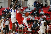 Minnehaha Academy's Hercy Miller (15) is fouled by Hopkins' Elvis Nnaji (15) as he drives for a layup Wednesday night. The Redhawks defeated the R