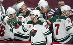 Minnesota Wild right wing Ryan Hartman, front, is congratulated as he passes the team box after scoring a goal against the Colorado Avalanche in the t
