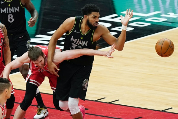 Chicago Bulls forward Luke Kornet, left, and Timberwolves center Karl-Anthony Towns battle for a loose ball during the first half