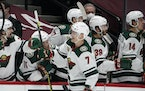 Minnesota Wild center Nico Sturm, front, is congratulated as he passes the team box after scoring a goal against the Colorado Avalanche during the thi