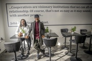 Alfred Sanders, left, and Keno Evol stood in the new space for Black Table Arts. Quotes from Black writers adorn the cooperative's south Minneapolis