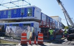 Prefabricated modules are stacked into place at a new apartment complex in Minneapolis.