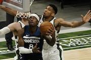 Minnesota Timberwolves' Jarred Vanderbilt shoots past Milwaukee Bucks' Giannis Antetokounmpo during the first half of an NBA basketball game Tuesd
