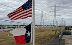 The U.S. and Texas flags fly in front of high-voltage transmission towers on Feb. 21, 2021, in Houston. President Joe Biden and his wife, Jill, are sc