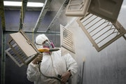Juan Salinas powder-coated decorative heat vents last week at JIT Powder Coating in Farmington. JIT used a $550,000 PPP loan to pay 60 employees for 1