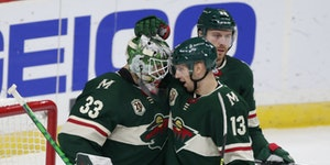 Minnesota Wild goalie Cam Talbot (33) is congratulated by center Nick Bonino (13) after defeating the Los Angeles Kings in an NHL hockey game, Friday,