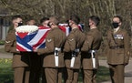 The coffin of Captain Tom Moore is carried by members of the armed forces during his funeral, at Bedford Crematorium, in Bedford, England, Saturday, F
