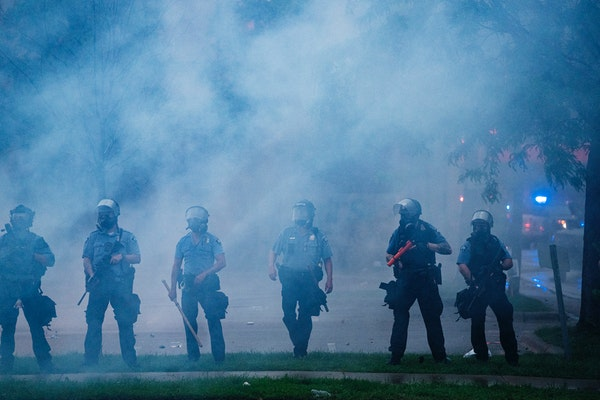 Police officers deployed to disperse protesters gathered for George Floyd in Minneapolis on Tuesday, May 26, 2020. During the rioting last year, metro