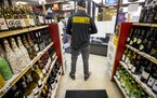 A security guard stood in an aisle at Greenway Liquors in Loring Park, where numerous looting incidents prompted the owner to put up boards on windows