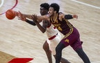 Nebraska center Eduardo Andre, left, and Minnesota's Eric Curry (24) reach for the ball during the second half of an NCAA college basketball game Sa
