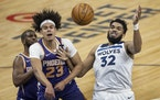 The Suns' Cameron Johnson and the Wolves' Karl-Anthony Towns tussled for the ball in the second quarter Sunday.