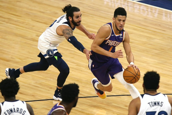 Devin Booker (1) drives the ball past Ricky Rubio (9) in the first half.