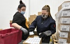 Employees with the McKesson Corporation scan a box of the Johnson & Johnson COVID-19 vaccine while filling an order at their shipping facility in Shep