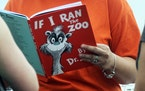 "In this Sept. 24, 2013, file photo, Courtney Keating, education coordinator of The Literacy Center in Evansville, Ind., reads ""If I Ran the Zoo,"""