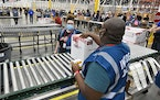 The first box containing the Johnson & Johnson COVID-19 vaccine heads down the conveyor to an awaiting transport truck at the McKesson facility in She