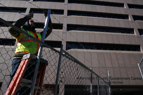 Izai Dominguez with Hansen Bros. Fence added barbed wire to the fencing around the Hennepin County Government Center as they worked to fortify the bui