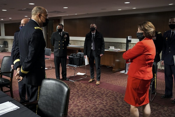 Army Maj. Gen. William Walker, Commanding General of the District of Columbia National Guard, speaks to Sen. Amy Klobuchar after a Senate joint hearin