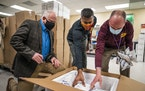 From left, Gov. Tim Walz watched as Dr. Abe Jacob and John Pastor unboxed a shipment of the Johnson & Johnson COVID-19 vaccine Wednesday at M Health F