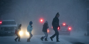 A group dashed across the street outside the Cathedral of St. Paul during a major winter storm in St. Paul.