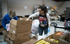 Volunteer Becky Geyer, of Edina, filled boxes of food as she volunteered with her mother Diane Haider, of Lake Elmo, left, at the Twin Cities Salvatio
