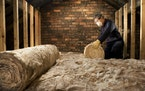man puts insulation in his loft