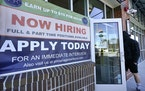 "A man walks into a restaurant displaying a ""Now Hiring"" sign, Thursday, March 4, 2021, in Salem, N.H. U.S. employers added a robust 379,000 jobs l"