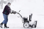 Joseph Long cleared a sidewalk in Minneapolis in February. Still might be too soon to store the snowblowers.