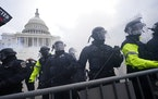 FILE - In this Jan. 6, 2021, file photo, police stand guard after holding off rioters who tried to break through a police barrier at the Capitol in Wa