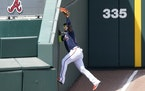 Atlanta left fielder Marcell Ozuna made a catch in foul territory to retire the Twins' Luis Arraez on Friday in North Port, Fla.