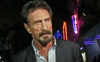 In this Dec. 12, 2012 file photo, anti-virus software founder John McAfee answers questions to reporters as he walks on Ocean Drive, in the South Beac