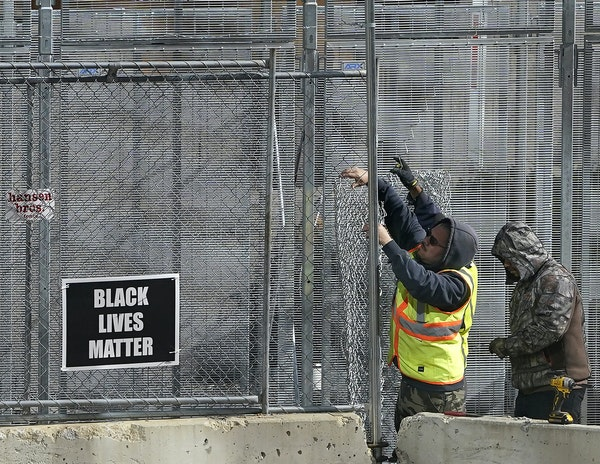 Workers finish a fencing perimeter outside the Hennepin County Government Center ahead of the trial of Derek Chauvin.