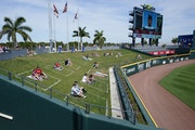 Fans were spaced apart in left field as they watched Friday's spring training game between the Twins and Braves in North Port, Fla.