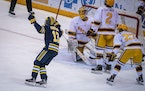 Michigan forward Kent Johnson (13), from left, celebrated a goal by Michigan forward Nick Granowicz (71) as Minnesota goaltender Jack LaFontaine (45),