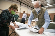 Duluth, Minnesota's 11th precinct co-head polling judges Kathie Trotta, left, and John Keenan place ballots into secure bags to be sealed and droppe