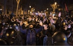 Demonstrators react as police cordon off the street during a march in Barcelona, Spain, Saturday, March 6, 2021.