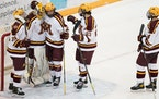 Minnesota forward Blake McLaughlin (27) gave a hug to goaltender Jack LaFontaine (45) after a victory over Michigan last March.