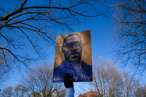 """Cortez Rice, who says he's a nephew of George Floyd by loyalty, not blood, held a """"Justice for George Floyd"""" sign at Saturday's protest in St."""