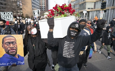 Cortez Rice, left, who is a friend of George Floyd, and Raj Sethuraju carried a mock coffin to mourn Floyd's killing during a rally Sunday in downto